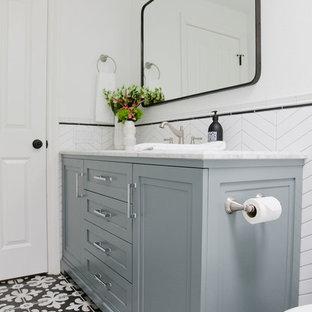 Idéer för mellanstora vintage grått badrum med dusch, med möbel-liknande, blå skåp, ett badkar i en alkov, en dusch/badkar-kombination, en toalettstol med hel cisternkåpa, vit kakel, porslinskakel, vita väggar, klinkergolv i porslin, ett undermonterad handfat, marmorbänkskiva, flerfärgat golv och dusch med duschdraperi