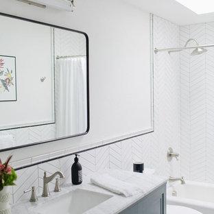 Inspiration för ett mellanstort vintage grå grått badrum med dusch, med möbel-liknande, blå skåp, ett badkar i en alkov, en dusch/badkar-kombination, en toalettstol med hel cisternkåpa, vit kakel, porslinskakel, vita väggar, klinkergolv i porslin, ett undermonterad handfat, marmorbänkskiva, flerfärgat golv och dusch med duschdraperi
