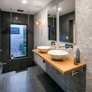 Inspiration for a contemporary 3/4 bathroom in Melbourne with a double shower, gray tile, a vessel sink and wood benchtops.
