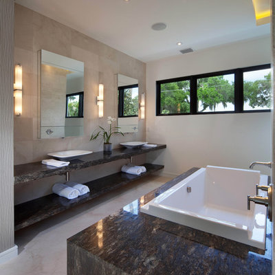 Example of a minimalist limestone tile bathroom design in Orlando with a vessel sink