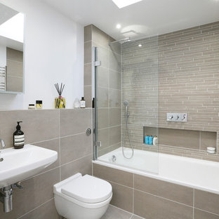 This is an example of a contemporary shower room in London with an alcove bath, a shower/bath combination, a wall mounted toilet, beige tiles, white walls, a wall-mounted sink, beige floors and a hinged door.
