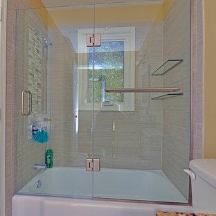 Exempel på ett mellanstort modernt badrum med dusch, med dusch med gångjärnsdörr, ett badkar i en alkov, en dusch/badkar-kombination, en toalettstol med hel cisternkåpa, beige kakel, porslinskakel, gula väggar, klinkergolv i porslin, granitbänkskiva och beiget golv