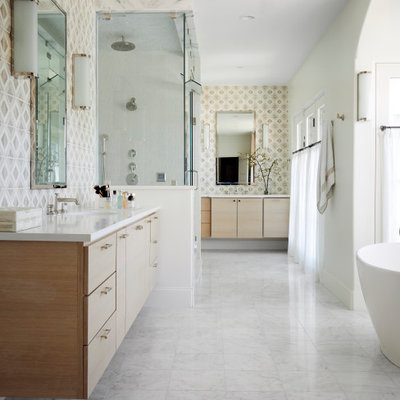 Inspiration for a mediterranean master beige tile double-sink and white floor bathroom remodel in Dallas with flat-panel cabinets, light wood cabinets, white walls, an undermount sink, a hinged shower door, white countertops and a floating vanity