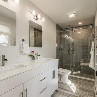 Foto på ett litet funkis en-suite badrum, med släta luckor, vita skåp, en dusch i en alkov, en toalettstol med hel cisternkåpa, grå kakel, porslinskakel, grå väggar, klinkergolv i porslin, ett undermonterad handfat, bänkskiva i kvarts, grått golv och dusch med skjutdörr