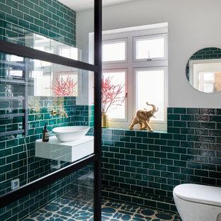 Foto på ett mellanstort funkis vit badrum med dusch, med öppna hyllor, vita skåp, en hörndusch, en vägghängd toalettstol, grön kakel, tunnelbanekakel, vita väggar, klinkergolv i keramik, ett fristående handfat, grönt golv och med dusch som är öppen
