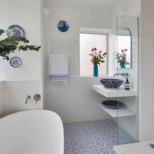 Inredning av ett modernt mellanstort vit vitt en-suite badrum, med öppna hyllor, vita skåp, ett fristående badkar, en dusch i en alkov, vit kakel, keramikplattor, vita väggar, mosaikgolv, ett fristående handfat och blått golv