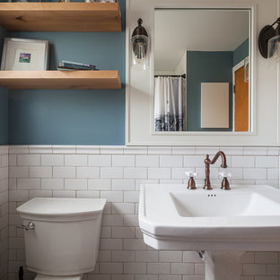 Mid-sized arts and crafts kids bathroom in Chicago with shaker cabinets, white cabinets, an alcove tub, a shower/bathtub combo, a two-piece toilet, white tile, subway tile, blue walls, ceramic floors, a pedestal sink, white floor and a shower curtain.