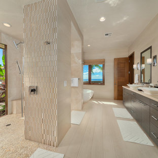 Large trendy master beige tile and porcelain tile beige floor and porcelain tile bathroom photo in Hawaii with flat-panel cabinets, dark wood cabinets, beige walls, a vessel sink and limestone countertops