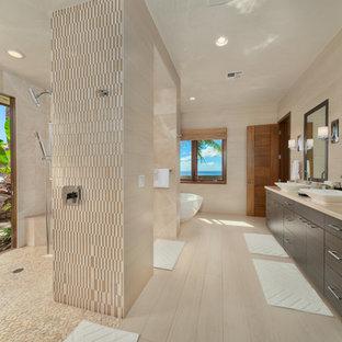 Idée de décoration pour une grand salle de bain principale design avec un placard à porte plane, des portes de placard en bois sombre, une douche ouverte, un carrelage beige, un mur beige, une vasque, un sol beige, un sol en carrelage de porcelaine, une baignoire indépendante, des carreaux de porcelaine, un plan de toilette en calcaire et aucune cabine.