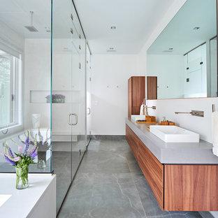 На фото: главная ванная комната в современном стиле с плоскими фасадами, фасадами цвета дерева среднего тона, душем без бортиков, белыми стенами, настольной раковиной, столешницей из бетона, серым полом, душем с распашными дверями и серой столешницей с