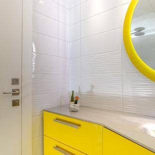 Ispirazione per una piccola stanza da bagno per bambini minimalista con ante di vetro, ante gialle, piastrelle bianche, piastrelle in gres porcellanato, pareti bianche, pavimento in gres porcellanato, pavimento grigio, top in vetro e top bianco