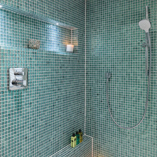 Coastal wet room in London with blue tiles, green tiles, mosaic tiles, green walls and grey floors.