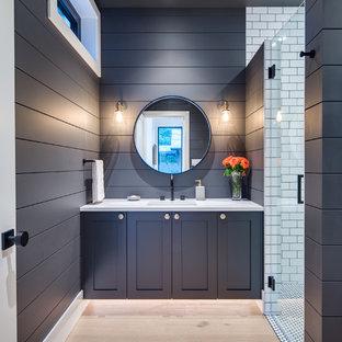 Idee per una stanza da bagno con doccia moderna di medie dimensioni con ante in stile shaker, ante blu, doccia ad angolo, WC monopezzo, piastrelle bianche, pareti blu, parquet chiaro, lavabo sottopiano, top in quarzite, porta doccia a battente e top bianco