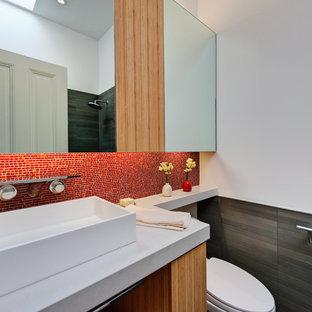 Aménagement d'une salle d'eau moderne de taille moyenne avec carrelage en mosaïque, une vasque, un carrelage rouge, un placard à porte plane, des portes de placard en bois brun, un WC séparé, un mur blanc et un plan de toilette en quartz modifié.