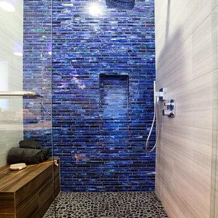 Imagen de cuarto de baño principal, moderno, de tamaño medio, con ducha a ras de suelo, baldosas y/o azulejos azules, baldosas y/o azulejos de vidrio, paredes blancas y suelo de baldosas tipo guijarro