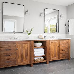 Bild på ett mellanstort maritimt vit vitt en-suite badrum, med möbel-liknande, skåp i mellenmörkt trä, vit kakel, keramikplattor, klinkergolv i porslin, ett undermonterad handfat, grått golv och grå väggar