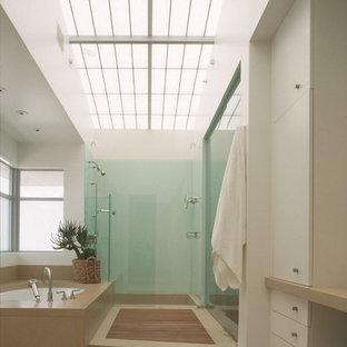Modelo de cuarto de baño moderno con armarios con paneles lisos, puertas de armario blancas, bañera encastrada sin remate y ducha empotrada