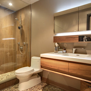 Example of a minimalist pebble tile floor alcove shower design in Toronto with an integrated sink, a one-piece toilet and white countertops