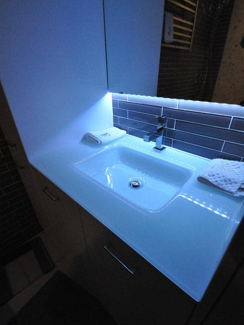 Salle de bain avec un plan de toilette en verre et un for Baignoire lavabo integre