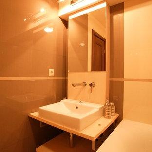 Foto di una piccola stanza da bagno per bambini contemporanea con lavabo a consolle, ante lisce, ante in legno chiaro, top in legno, vasca da incasso, WC sospeso, piastrelle beige, piastrelle in ceramica, pareti beige e pavimento con piastrelle in ceramica