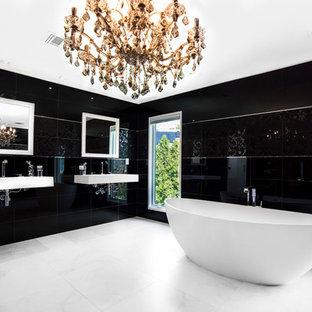 Imagen de cuarto de baño principal, minimalista, grande, con lavabo integrado, armarios abiertos, puertas de armario blancas, encimera de cuarzo compacto, bañera exenta, ducha esquinera, sanitario de una pieza, baldosas y/o azulejos negros, baldosas y/o azulejos de vidrio laminado, paredes negras y suelo de cemento
