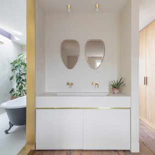This is an example of a medium sized modern ensuite bathroom in Cheshire with flat-panel cabinets, white cabinets, a claw-foot bath, white walls, medium hardwood flooring, a submerged sink, brown floors and white worktops.
