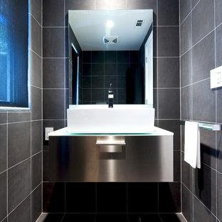 Пример оригинального дизайна: маленькая ванная комната в стиле модернизм с настольной раковиной, столешницей из нержавеющей стали, серой плиткой, керамической плиткой, серыми стенами, полом из керамической плитки, душевой кабиной, плоскими фасадами и серым полом