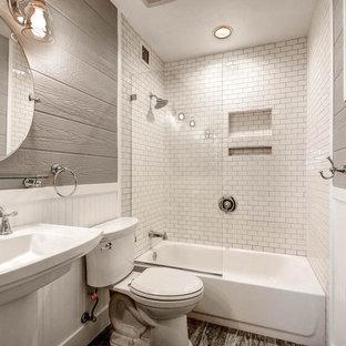 Foto på ett litet funkis badrum, med ett badkar i en alkov, en dusch/badkar-kombination, en toalettstol med hel cisternkåpa, vit kakel, tunnelbanekakel, grå väggar, mellanmörkt trägolv, ett piedestal handfat och bänkskiva i akrylsten