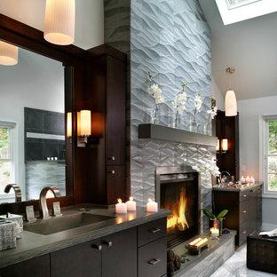 Esempio di una stanza da bagno contemporanea di medie dimensioni con ante lisce, top in cemento, WC monopezzo, lavabo integrato, ante in legno bruno, piastrelle grigie, piastrelle in gres porcellanato, pareti bianche e top grigio