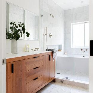 Пример оригинального дизайна: главная ванная комната среднего размера в стиле модернизм с фасадами островного типа, фасадами цвета дерева среднего тона, полновстраиваемой ванной, открытым душем, унитазом-моноблоком, белой плиткой, каменной плиткой, белыми стенами, мраморным полом, монолитной раковиной, столешницей из искусственного кварца, белым полом, открытым душем и белой столешницей