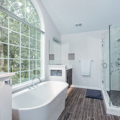 Example of a large minimalist master white tile and porcelain tile porcelain tile and brown floor bathroom design in DC Metro with shaker cabinets, dark wood cabinets, a two-piece toilet, gray walls, an undermount sink, quartz countertops, a hinged shower door and white countertops
