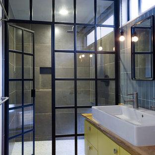 На фото: ванная комната в стиле лофт с настольной раковиной, столешницей из дерева, желтыми фасадами и коричневой столешницей с