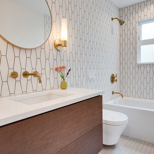 Mid-sized trendy white tile and cement tile ceramic floor and white floor bathroom photo in Seattle with flat-panel cabinets, medium tone wood cabinets, a one-piece toilet, white walls, a drop-in sink, quartzite countertops and white countertops