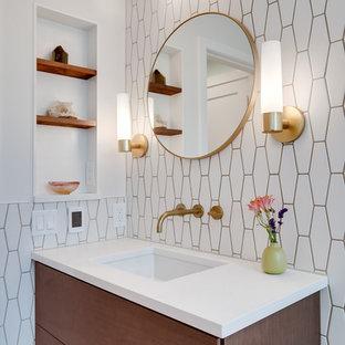 シアトルの中サイズのモダンスタイルのおしゃれな浴室 (フラットパネル扉のキャビネット、中間色木目調キャビネット、ドロップイン型浴槽、シャワー付き浴槽、一体型トイレ、白いタイル、セメントタイル、白い壁、セラミックタイルの床、オーバーカウンターシンク、珪岩の洗面台、シャワーカーテン、白い洗面カウンター) の写真