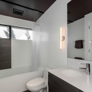 Example of a minimalist white tile bathroom design in San Francisco with an undermount sink, flat-panel cabinets, dark wood cabinets and a one-piece toilet
