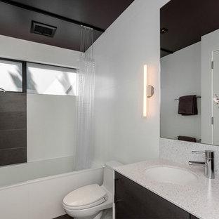Esempio di una stanza da bagno minimalista con lavabo sottopiano, ante lisce, ante in legno bruno, vasca ad alcova, vasca/doccia, WC monopezzo e piastrelle bianche