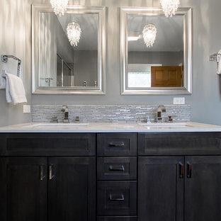 Пример оригинального дизайна: главная ванная комната среднего размера в стиле модернизм с врезной раковиной, фасадами в стиле шейкер, столешницей из искусственного кварца, душем в нише, унитазом-моноблоком, серой плиткой, серыми стенами, темными деревянными фасадами и металлической плиткой