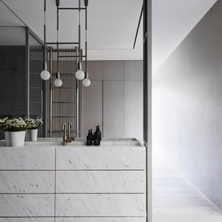 This is an example of a modern bathroom in Sydney with flat-panel cabinets, white cabinets, grey walls, an integrated sink, grey floor, white benchtops, a single vanity and a freestanding vanity.