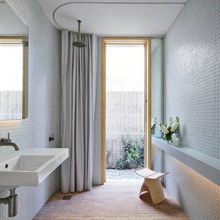 Ejemplo de cuarto de baño minimalista con ducha a ras de suelo, baldosas y/o azulejos grises, baldosas y/o azulejos en mosaico, suelo de ladrillo, lavabo suspendido, suelo marrón y ducha con cortina