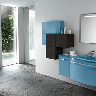Immagine di una piccola stanza da bagno con doccia minimalista con lavabo integrato, ante lisce, ante blu, top in vetro, vasca freestanding, doccia ad angolo, WC monopezzo, piastrelle grigie, piastrelle in ceramica, pareti grigie e pavimento con piastrelle in ceramica