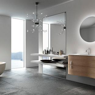 Imagen de cuarto de baño con ducha, moderno, pequeño, con lavabo integrado, armarios tipo mueble, puertas de armario de madera clara, encimera de vidrio, bañera exenta, sanitario de dos piezas, baldosas y/o azulejos blancos, baldosas y/o azulejos de cerámica, paredes beige y suelo de azulejos de cemento