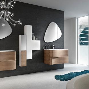 Ejemplo de cuarto de baño moderno, pequeño, con lavabo integrado, armarios tipo mueble, puertas de armario azules, bañera exenta, ducha esquinera, sanitario de dos piezas, baldosas y/o azulejos grises, baldosas y/o azulejos de cerámica, paredes negras y suelo de azulejos de cemento