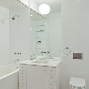Example of a minimalist bathroom design in New York with an undermount sink and a wall-mount toilet