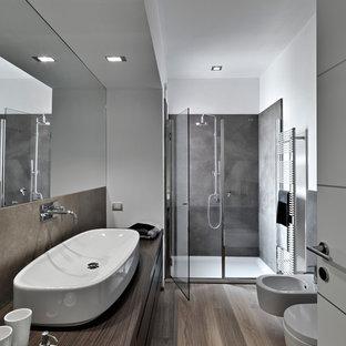 Idéer för mellanstora funkis brunt badrum, med släta luckor, skåp i mörkt trä, en dusch i en alkov, en bidé, vita väggar, laminatgolv, ett fristående handfat, träbänkskiva och dusch med gångjärnsdörr