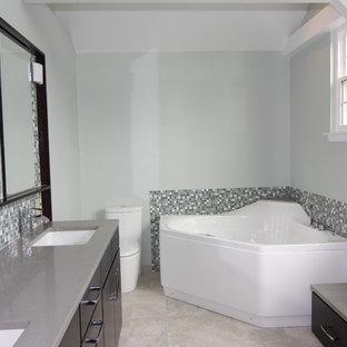 Imagen de cuarto de baño principal, actual, grande, con lavabo bajoencimera, armarios con paneles lisos, puertas de armario de madera en tonos medios, encimera de cuarcita, bañera esquinera, ducha esquinera, sanitario de una pieza, baldosas y/o azulejos grises, baldosas y/o azulejos de porcelana, paredes azules y suelo de baldosas de porcelana