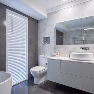 Mittelgroßes Modernes Badezimmer En Suite mit Schrankfronten mit vertiefter Füllung, weißen Schränken, Eckbadewanne, Eckdusche, Toilette mit Aufsatzspülkasten, grauen Fliesen, Keramikfliesen, grauer Wandfarbe, Keramikboden, integriertem Waschbecken, Mineralwerkstoff-Waschtisch, grauem Boden, Falttür-Duschabtrennung, weißer Waschtischplatte, Einzelwaschbecken und schwebendem Waschtisch in Sonstige