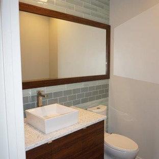 Modelo de cuarto de baño con ducha, minimalista, pequeño, con armarios con paneles lisos, puertas de armario de madera en tonos medios, suelo marrón, sanitario de una pieza, baldosas y/o azulejos grises, baldosas y/o azulejos de vidrio, paredes grises, suelo de madera oscura, lavabo sobreencimera y encimera de vidrio reciclado