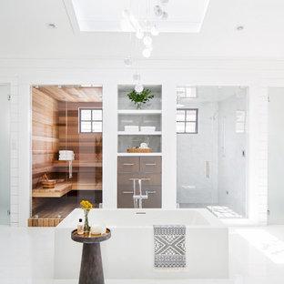 Foto di una stanza da bagno costiera con vasca freestanding, doccia alcova, pareti bianche, pavimento bianco e porta doccia a battente