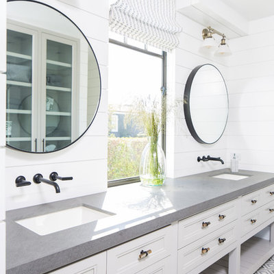 Inspiration for a coastal gray floor bathroom remodel in Orange County with recessed-panel cabinets, white cabinets, white walls, an undermount sink and gray countertops