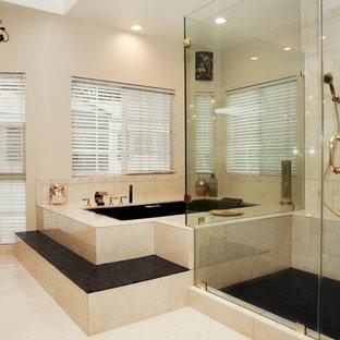 На фото: огромная главная ванная комната в стиле модернизм с фасадами с выступающей филенкой, фасадами цвета дерева среднего тона, гидромассажной ванной, угловым душем, унитазом-моноблоком, бежевой плиткой, керамической плиткой, бежевыми стенами, полом из керамической плитки, настольной раковиной и столешницей из гранита с